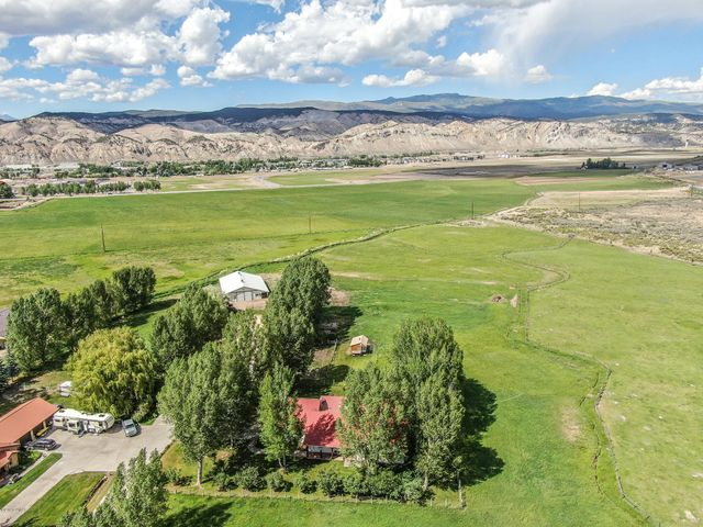 Opportunity to own 9.37 flat acres with Town water and irrigation water. Property touches BLM, has 30 x 35 three car attached garage, plus 3200sf shop with half bath, heat and sound system, and 3150 sf barn that can be used for most animals including horses. One level home with spacious kitchen, living room and master. Huge covered deck in the back with views of Castle peak. One of a kind.