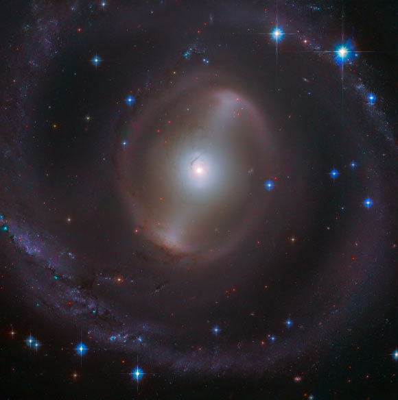 This Hubble image shows the central region of NGC 2217, a barred spiral galaxy some 83 million light-years away in the constellation Canis Major. This image is made up of observations from Hubble's Advanced Camera for Surveys (ACS) in the optical part of the spectrum. It was colorized with data from the Panoramic Survey Telescope and Rapid Response System (Pan-STARRS). Image credit: NASA / ESA / Hubble / J. Dalcanton / Judy Schmidt, www.geckzilla.com.
