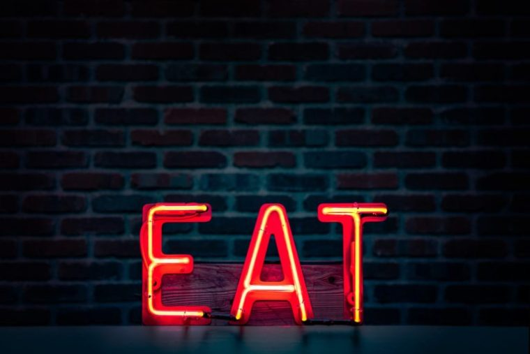 A neon sign with the letters E-A-T