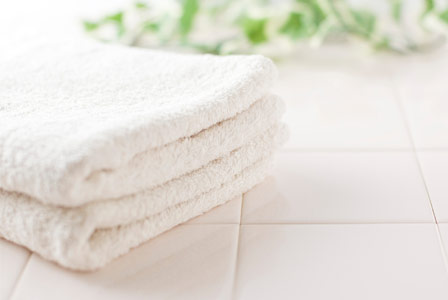 Organic bath towels on white tile