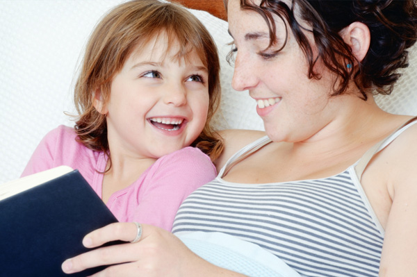 mom reading chapter book with daughter