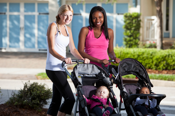 Two moms stand next to each other with their babies in strollers