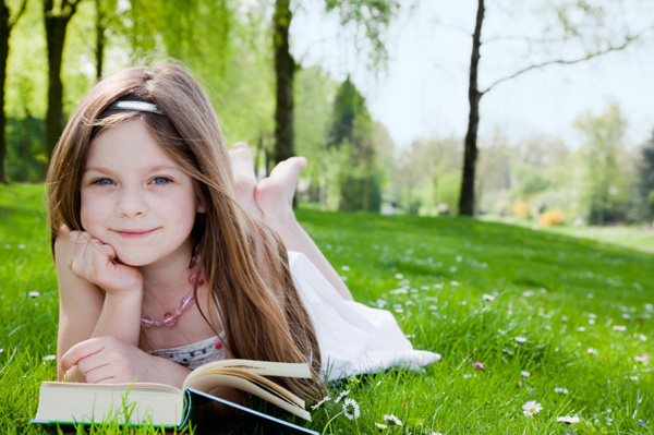 little girl reading book outside