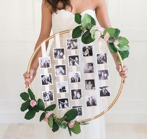 Varal de fotos de casamento em arco circular, com noiva o segurando. Imagem Pinterest via We Are Ideas