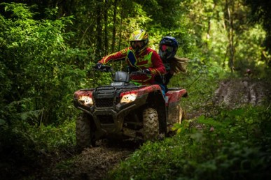 imagem de um casal em meio à floresta em um quadriciclo em velocidade