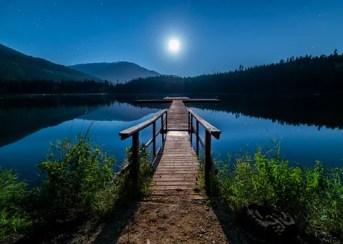 lua iluminando um lago e ponte que liga a um campo
