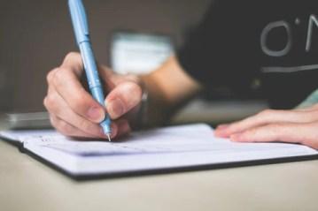 mão de rapaz fazendo anotações em um caderno