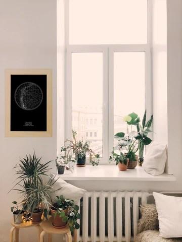 Imagem de quadro do Mapa do Céu preto na parede de uma sala clara, próximo a uma janela com muitas plantas, um sofá e uma janela