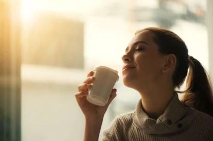 moça com os olhos fechados tomando café com satisfação