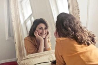 mulher apoiada em bancada sorri olhando para espelho