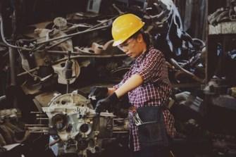mulher trabalha com capacete em fábrica de veículos