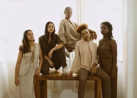 mulheres de várias etnias sentadas e apoiadas em uma mesa, olhando para câmera em pose de poder