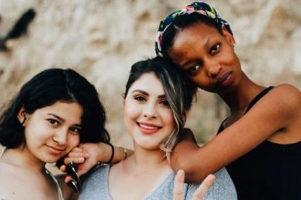 três mulheres de etnias e corpos bem distintos apoiadas umas nas outras