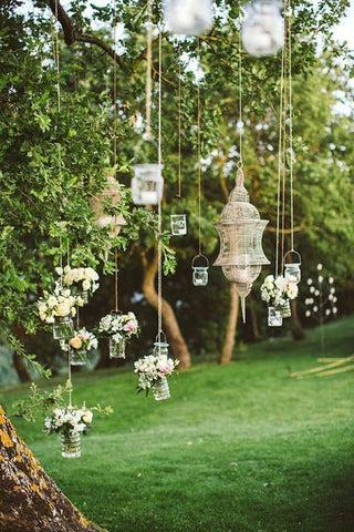 velas penduradas em vidros, pendurados em árvore. Imagem Pinterest via Sortra
