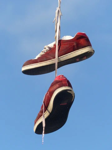 Shoes hanging down - representing testicles hanging outside the body for cooling.