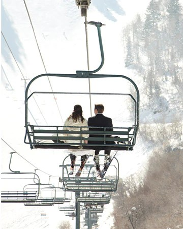 Bride and Groom riding a ski chairlift.