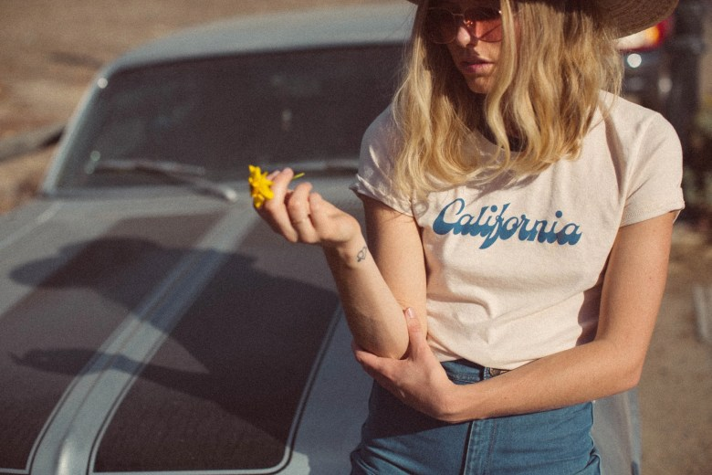 "Image of a model sitting on a car wearing a t-shirt that reads ""California"""