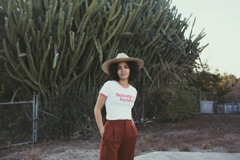 "Woman in a hat and t-shirt that says ""Nobody's Perfekt"" stands against a background of trees"