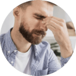 Man with headache holding nose bridge