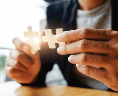 Woman fitting puzzle pieces together