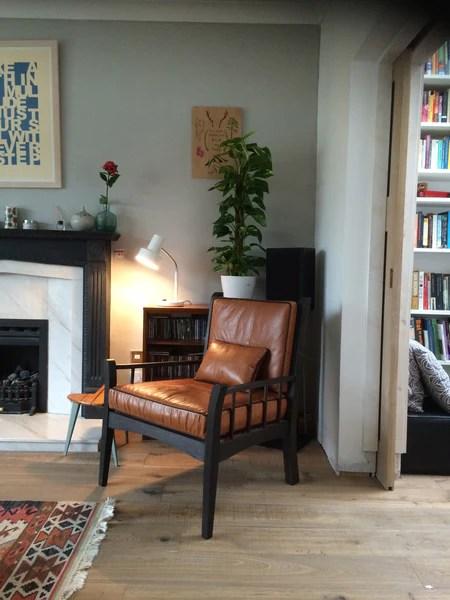 handmade wooden chair, grey wall, built in bookcase, wooden floor, oriental rug