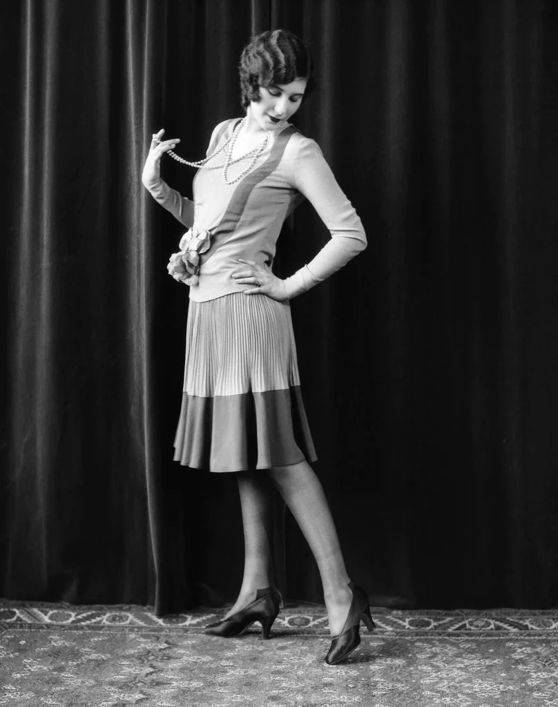 1920s Flapper Woman Posing Hand On Hip Holding String Of ...