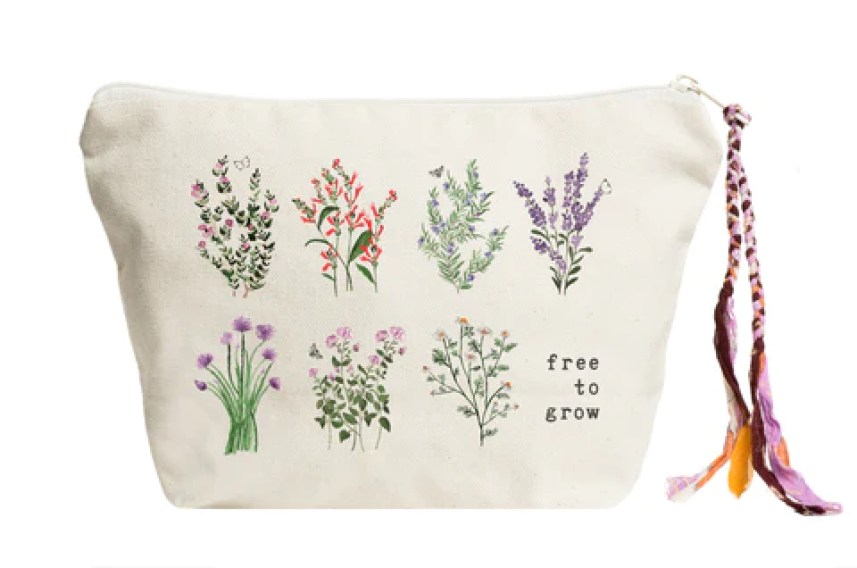 White makeup bag from The Tote Project with 'free to grow' text