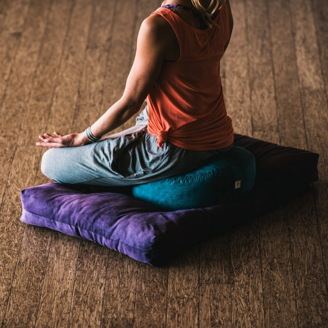 Teal zafu meditation cushion woman sitting on top