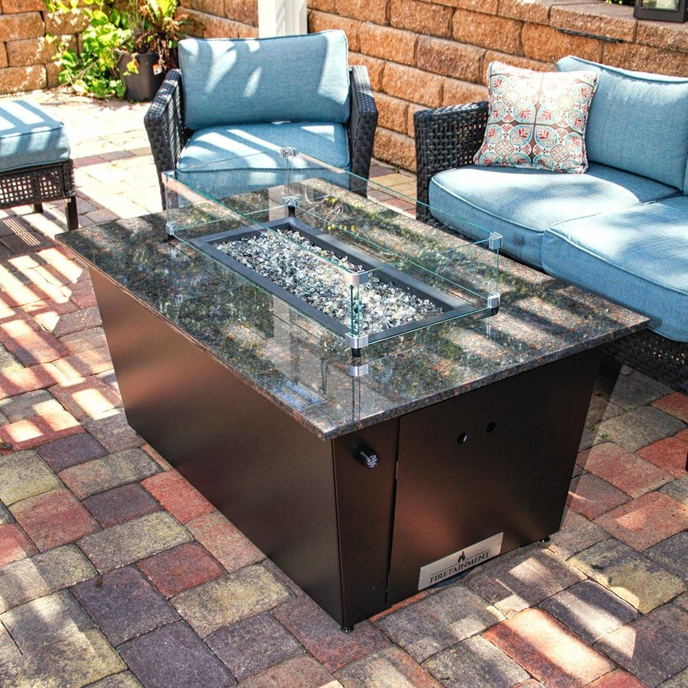 monaco fire table with brown granite top and glass wind guard