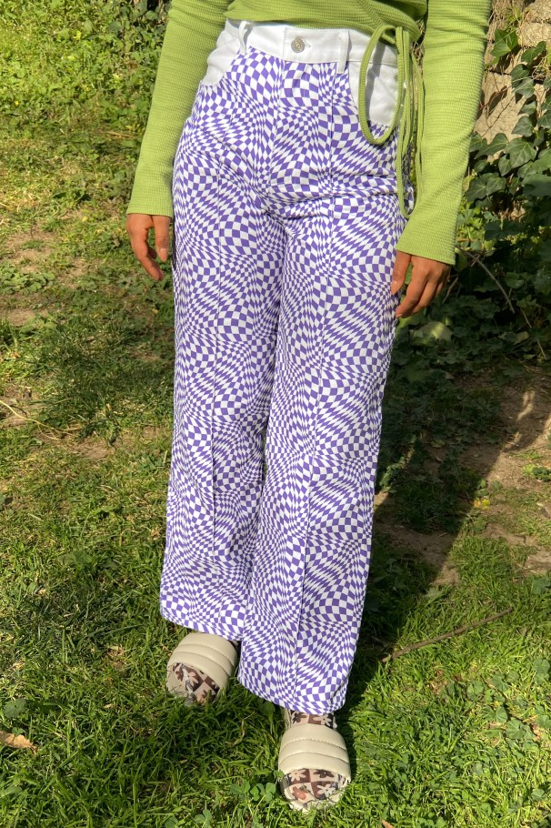 Woman wears green long sleeve top with cow and checkerboard purple and white jeans with socks and slides