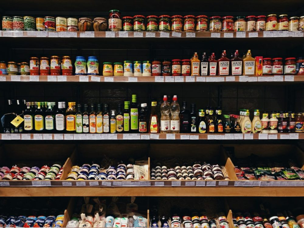 Busy grocery store shelves with oils and other items.