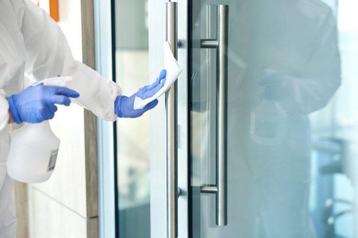 Person Disinfecting Door