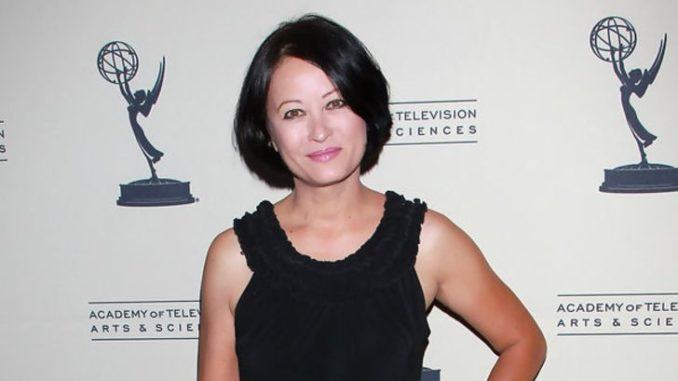 A woman with a bob cut and a black dress at an event.