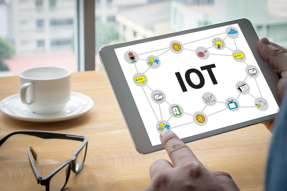 A man uses a tablet to open up IoT home capabilities
