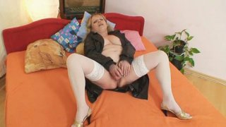 Image: Horny older lady wears stockings and toys herself