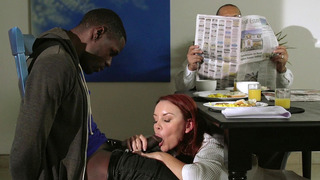 Janet Mason starts sucking on her stepson's black cock while her husband reads the paper image