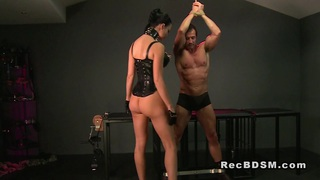 Tied up slave gets cock flogged and ass plugged image