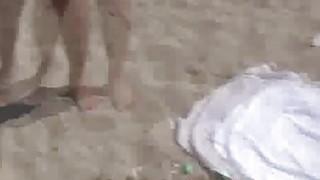 Oily teen flashing on the beach image