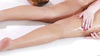 Naked tanned brunette gets lesbian massage image