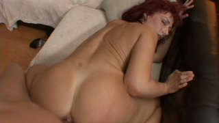 Fat ass Nikki Sinn riding cock on a couch and stimulating her asshole image