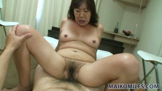 Filthy mature woman Michiko Okawa rides cock with her hairy pussy image
