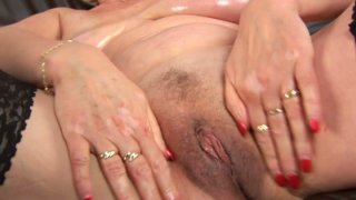 Busty granny Janka oils her big tits and fingers her old snatch image