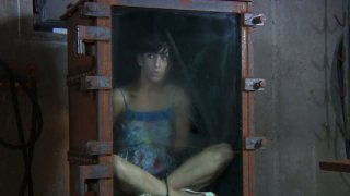 Brunette Elise Graves is locked into a small glass box image