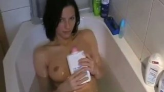 Saucy amateur chick bathes in a bath tub and sucks her man's cock image