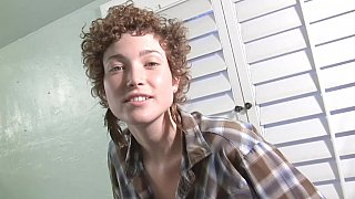 Curly babe is fooling around in a bathtub image