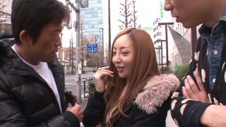 Neat and tiny Erena Aihara gets seduced on a street and agrees for a threesome sex in a porn video image