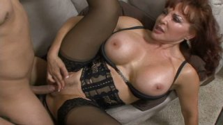 Busty redhead milf is dressed in_sexy lingerie and stockings image