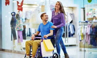 A man in a wheelchair and a woman laughing and shopping