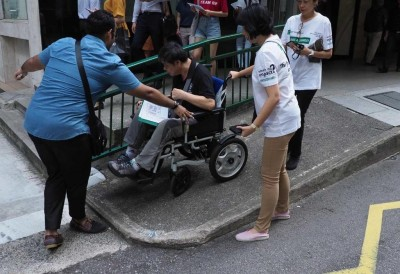 Two people helping a person navigate streets on a wheehlchair