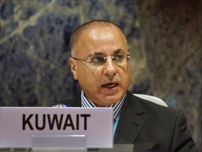 Male person speaking at conference with country placard reading kuwait in front of him.
